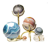 Assortment of egg & sphere display stands (high risers and other styles) shown here are just a few of our brass, gold plated brass, clear lucite, and acrylic styles available. Collection displayed is just a sampling of our Brazilian agate spheres you can choose from in our Newport, Oregon showroom.  We are open daily 10:00 a.m. to 5:00 p.m. year round, for your shopping pleasure!